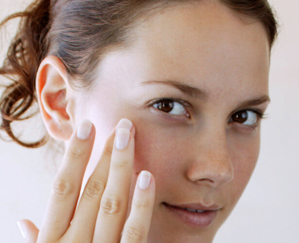 Woman using Johnson's® baby oil for adult skin care on face