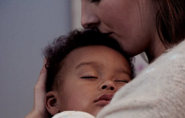 Madre con figlio che dorme tra le sue braccia